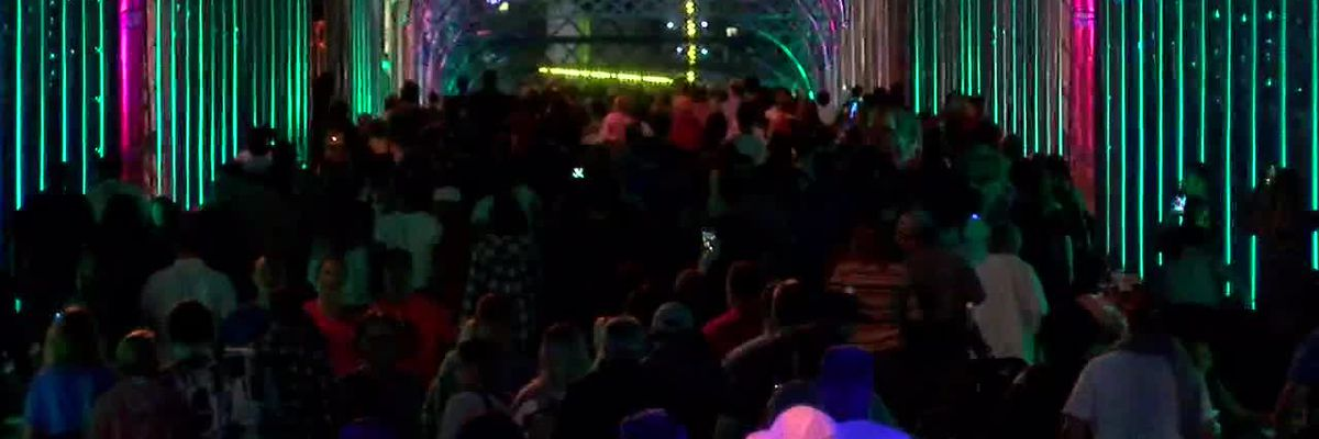 People walking over the lit up Roebling Bridge for BLINK